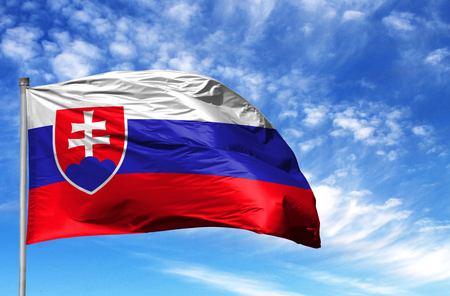 National flag of Slovakia on a flagpole in front of blue sky.