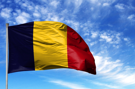National flag of Chad on a flagpole in front of blue sky.
