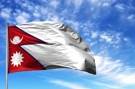 National flag of Nepal on a flagpole in front of blue sky.