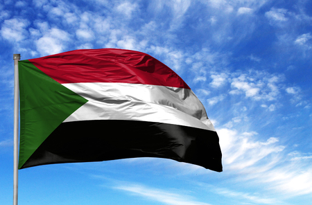 National flag of Sudan on a flagpole in front of blue sky.