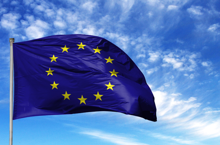 National flag of European Union on a flagpole in front of blue sky.