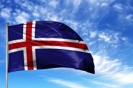 National flag of Iceland on a flagpole in front of blue sky.