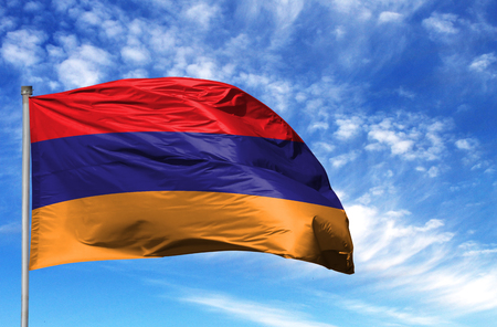 National flag of Armenia on a flagpole in front of blue sky. Stockfoto