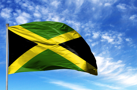 National flag of Jamaica on a flagpole in front of blue sky. Stock Photo