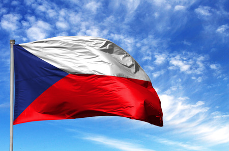 National flag of Czech Republic on a flagpole in front of blue sky.