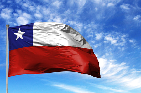 National flag of Chile on a flagpole in front of blue sky.