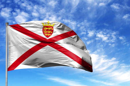 National flag of Jersey on a flagpole in front of blue sky.