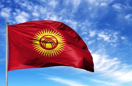 National flag of Kyrgyzstan on a flagpole in front of blue sky.