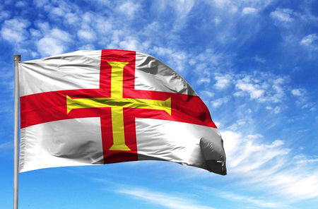 National flag of Guernsey on a flagpole in front of blue sky. 写真素材