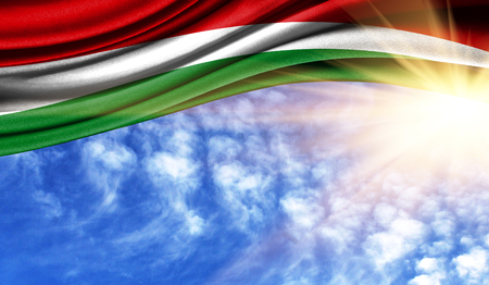 the flag of Hungary in the rays of the summer sun, in the sky, photography has a good place for your text.