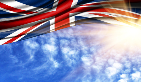 the flag of United Kingdom in the rays of the summer sun, in the sky, photography has a good place for your text. Stock Photo