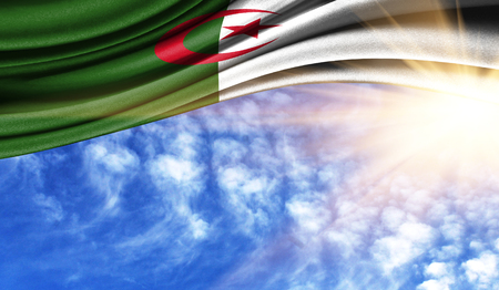 the flag of Algeria in the rays of the summer sun, in the sky, photography has a good place for your text. Stock Photo
