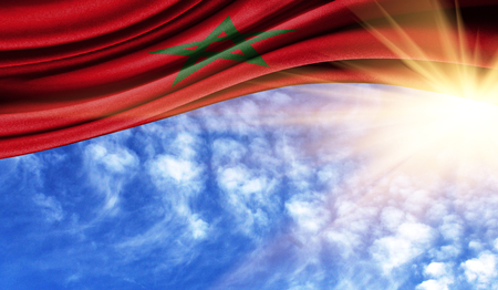 the flag of Morocco in the rays of the summer sun, in the sky, photography has a good place for your text.