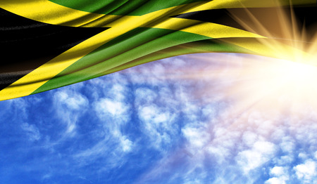 the flag of Jamaica in the rays of the summer sun, in the sky, photography has a good place for your text.