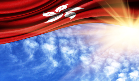 the flag of Hong Kong in the rays of the summer sun, in the sky, photography has a good place for your text.