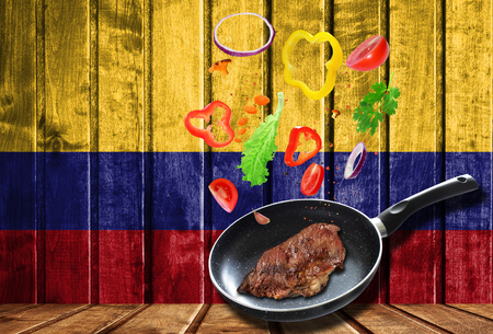 Cooking process. Hot movement. Fresh vegetables falling into the pan with meat, cooking concept on wooden flag background of Colombia Banque d'images