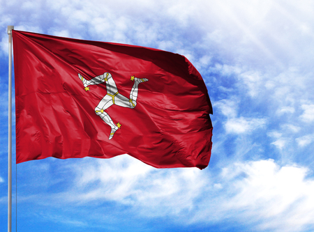 National flag of Isle Of Man on a flagpole in front of blue sky. Stock Photo