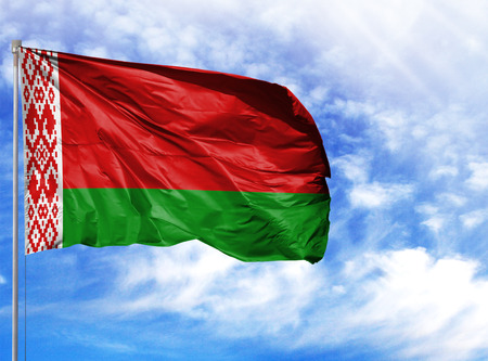 National flag of Belarus on a flagpole in front of blue sky.