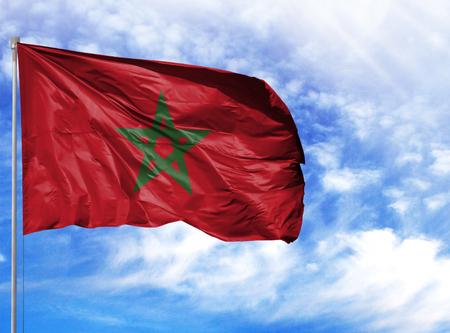 Drapeau national du Maroc sur un mât en face de ciel bleu.