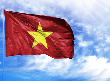 National flag of Vietnam on a flagpole in front of blue sky.