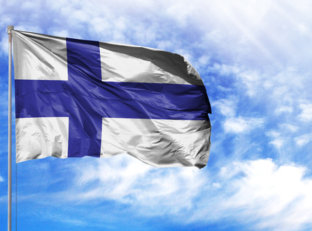 National flag of Finland on a flagpole in front of blue sky.