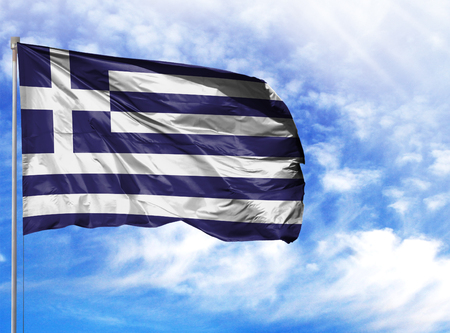 National flag of Greece on a flagpole in front of blue sky.