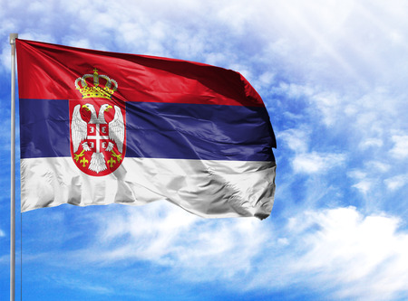 National flag of Serbia on a flagpole in front of blue sky. Stockfoto