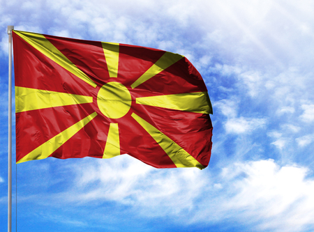 National flag of Macedonia on a flagpole in front of blue sky.