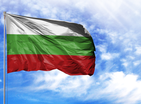 National flag of Bulgaria on a flagpole in front of blue sky. 스톡 콘텐츠