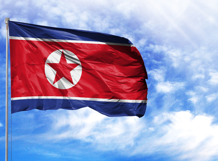 National flag of North Korea on a flagpole in front of blue sky. Banco de Imagens