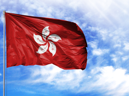 National flag of Hong Kong on a flagpole in front of blue sky. Stockfoto