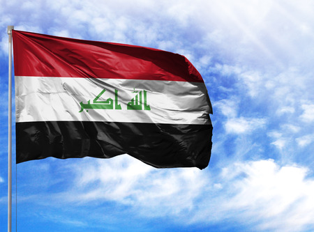National flag of Iraq on a flagpole in front of blue sky.