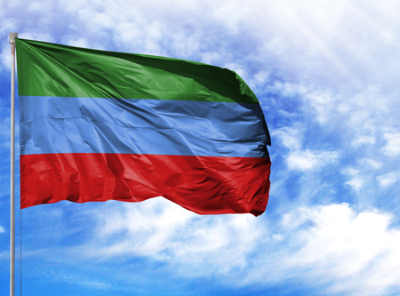 National flag of Dagestan on a flagpole in front of blue sky. Stock Photo