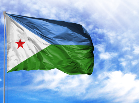 National flag of Djibouti on a flagpole in front of blue sky. Stockfoto