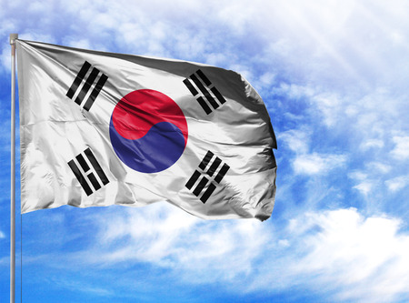 National flag of South Korea on a flagpole in front of blue sky.