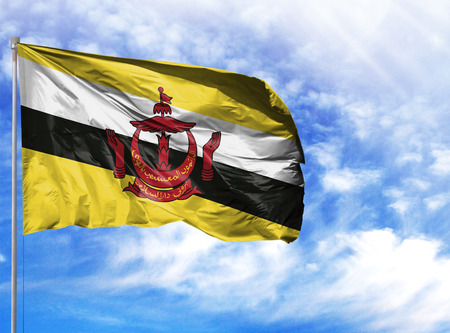 National flag of Brunei on a flagpole in front of blue sky.