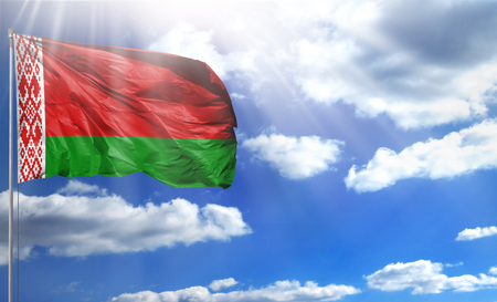 Flag of Belarus on a flagpole against a blue sky, with a good place for your text. Stock Photo