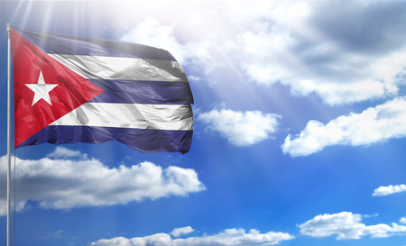 Flag of Cuba on a flagpole against a blue sky, with a good place for your text.