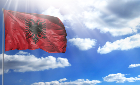 Flag of Albania on a flagpole against a blue sky, with a good place for your text.