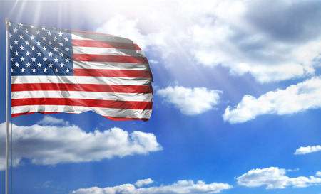 Flag of USA on a flagpole against a blue sky, with a good place for your text.