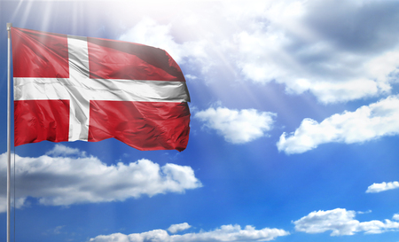 Flag of Denmark on a flagpole against a blue sky, with a good place for your text.