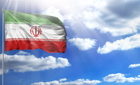 Flag of Iran on a flagpole against a blue sky, with a good place for your text. Imagens