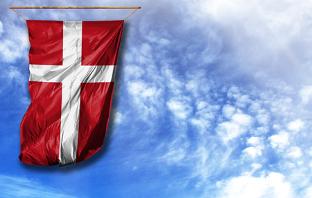 Flag of Denmark. Vertical flag, against blue sky with place for your text