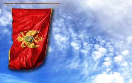 Flag of Montenegro. Vertical flag, against blue sky with place for your text