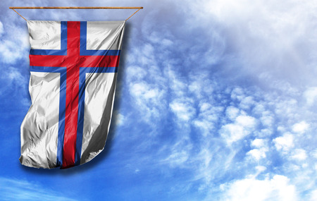 Flag of Faroe Islands. Vertical flag, against blue sky with place for your text