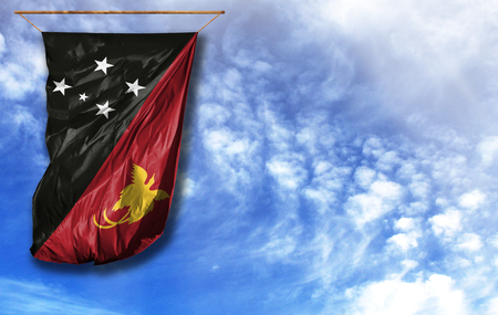 Flag of Papua New Guinea. Vertical flag, against blue sky with place for your text