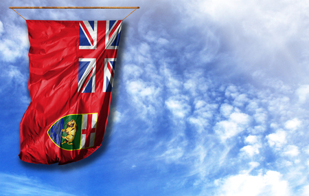 Flag of Manitoba. Vertical flag, against blue sky with place for your text