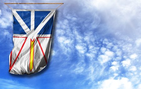 Flag of Newfoundland and Labrador. Vertical flag, against blue sky with place for your text