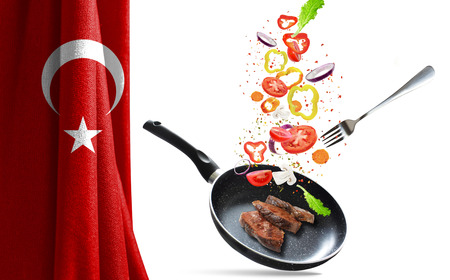 Frying pan with falling vegetables and meat, isolated objects. On the background of the flag of Turkey