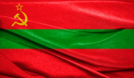 Realistic flag of Transnistria on the wavy surface of fabric. Perfect for background or texture purposes.